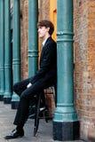 Nachdenklicher Geschäftsmann, der nahe bei einer Wand sitzt stockfotografie