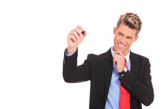 Nachdenklicher Geschäftsmann schreibt etwas Lizenzfreie Stockfotos