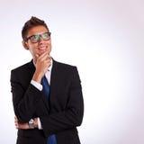 Nachdenklicher Geschäftsmann, der oben zu etwas schaut Stockfotografie