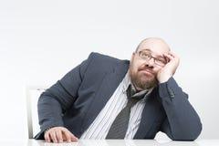 Nachdenklicher Geschäftsmann, der am Tisch sitzt Lizenzfreie Stockbilder