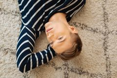 Nachdenklicher Jugendlicher, der auf dem Boden und dem Denken liegt Lizenzfreie Stockfotos