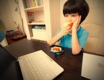 Nachdenklicher Junge, der mit einem Laptop sitzt und Apfel isst Lizenzfreie Stockfotos
