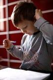 Nachdenklicher Junge in einem roten Stuhl am Tisch stockbild