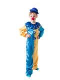 Nachdenklicher Junge gekleidet als Clown mit dem Händchenhalten einer Rotnase auf Flanken und Schauen zur Seite stockfotos