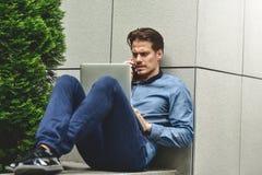 Nachdenklicher junger kaukasischer Mann, der Laptop verwendet, um online zu plaudern Lizenzfreies Stockfoto