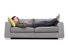 Nachdenklicher junger Kerl, der auf ein Sofa legt Stockfotos