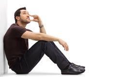 Nachdenklicher junger Mann, der auf dem Boden sitzt und oben schaut Stockbilder