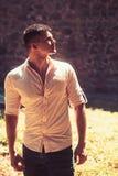 Nachdenklicher junger Mann im Hemd, das im Freien steht und denkt stockfotografie