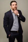 Nachdenklicher junger Mann im intelligenten casualwear, das seinen Bart berührt lizenzfreie stockbilder