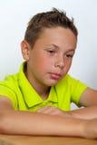 Nachdenklicher kaukasischer Junge, der am Tisch sitzt Stockfotografie