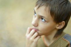 Nachdenklicher kleiner Junge im Herbst Stockfotos