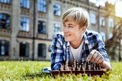 Nachdenklicher lächelnder Kerl beim Spielen des Schachs Lizenzfreie Stockbilder