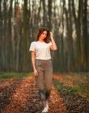 Nachdenklicher Mädchenweg herum im Wald bei Sonnenuntergang lizenzfreies stockbild