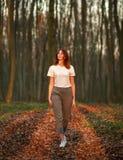Nachdenklicher Mädchenweg herum im Wald bei Sonnenuntergang stockbilder