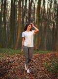 Nachdenklicher Mädchenweg herum im Wald bei Sonnenuntergang lizenzfreie stockfotografie