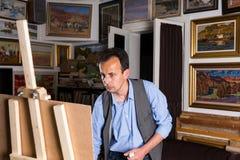 Nachdenklicher männlicher Künstler konzentrierte sich auf das Malen seines Bildes Stockfotografie