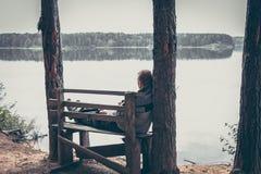 Nachdenklicher Mann auf dem hohen Rand von Flussbank sitzend auf der Bank und schauend auf schöner Landschaft mit ruhigem Wasser Stockbild