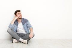 Nachdenklicher Mann, der auf Boden sitzt und aufwärts schaut Stockfotos