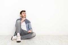 Nachdenklicher Mann, der auf Boden sitzt und aufwärts schaut Stockfotografie