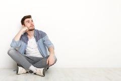 Nachdenklicher Mann, der auf Boden sitzt und aufwärts schaut Lizenzfreies Stockbild