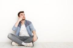 Nachdenklicher Mann, der auf Boden sitzt und aufwärts schaut Lizenzfreie Stockfotos