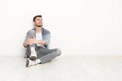Nachdenklicher Mann, der auf Boden sitzt und aufwärts schaut Stockbilder