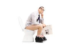 Nachdenklicher Mann, der auf Toilette sitzt und ein Papier hält Stockbilder