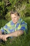 Nachdenklicher Mann, der im Gras sitzt Stockfotos