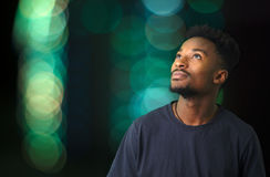 Nachdenklicher Mann, der träumerische grün-blaue belichtete Atmosphäre des Himmels schaut Lizenzfreies Stockfoto