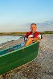 Nachdenklicher Mann in einem Boot auf der Küste Lizenzfreie Stockfotos
