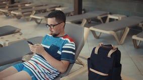 Nachdenklicher Mann surft Internet durch seinen Handy und liegt auf Ruhesessel in der Tageszeit stock video footage