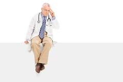 Nachdenklicher reifer Doktor, der auf einer Leerplatte sitzt Stockbild
