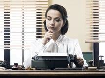 Nachdenklicher Sekretär mit Schreibmaschine Stockfotos