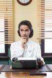 Nachdenklicher Sekretär mit Schreibmaschine Lizenzfreie Stockbilder