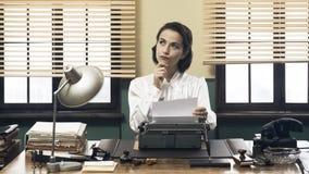 Nachdenklicher Sekretär mit Schreibmaschine Stockfoto