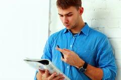 Nachdenklicher Student, der sein Notizbuch liest Stockfotos
