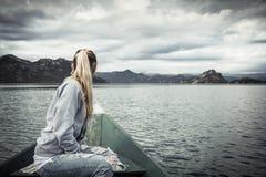 Nachdenklicher Tourist der jungen Frau, der schöne Landschaft auf dem Bogen des Bootes schwimmend auf Wasser in Richtung zum Ufer Lizenzfreie Stockbilder