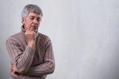 Nachdenklicher trauriger reifer Mann, der seine Hand unter seinem Kinn unten schaut mit dem unglücklichen Ausdruck denkt an etwas Lizenzfreie Stockbilder