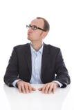 Nachdenklicher und zweifelhafter lokalisierter Geschäftsmann, der die Seite wir betrachtet Stockbilder