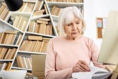 Nachdenkliches älteres Frauenlesebuch lizenzfreies stockbild