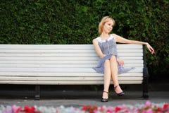 Nachdenkliches blondes Sitzen auf Bank Lizenzfreie Stockfotografie