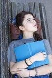 Nachdenkliches Hippie-Mädchen, das auf Bank mit blauem Buch, Adoleszenz lifestyl liegt Lizenzfreies Stockfoto