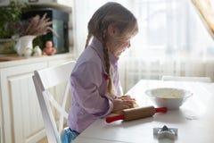 Nachdenkliches kaukasisches Mädchen rollt den Teig mit einem Nudelholz, littl lizenzfreie stockfotografie