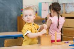 Nachdenkliches Kind, das im Kindergarten spielt stockfotos