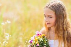 Nachdenkliches Mädchen, das auf Feld stillsteht Lizenzfreies Stockbild
