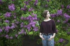 Nachdenkliches Mädchen, das in den Fliederbüschen im Park aufwirft lizenzfreie stockfotos