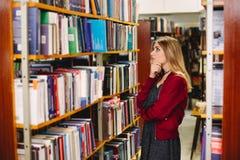 Nachdenkliches Mädchen, das ein Buch in der Collegebibliothek chosing ist getrennte alte Bücher Lizenzfreies Stockfoto