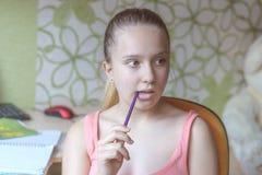Nachdenkliches Mädchen, das einen Bleistift in ihrem Mund hält lizenzfreies stockfoto