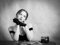 Nachdenkliches Mädchen im Abendkleid, das bei Tisch mit Zeitschriften sitzt lizenzfreie stockbilder
