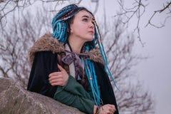 Nachdenkliches Mädchen mit blauen Haar Dreadlocks im Wald auf den Felsen Frauenwikinger-Träume und -blicke in den Abstand lizenzfreie stockfotos